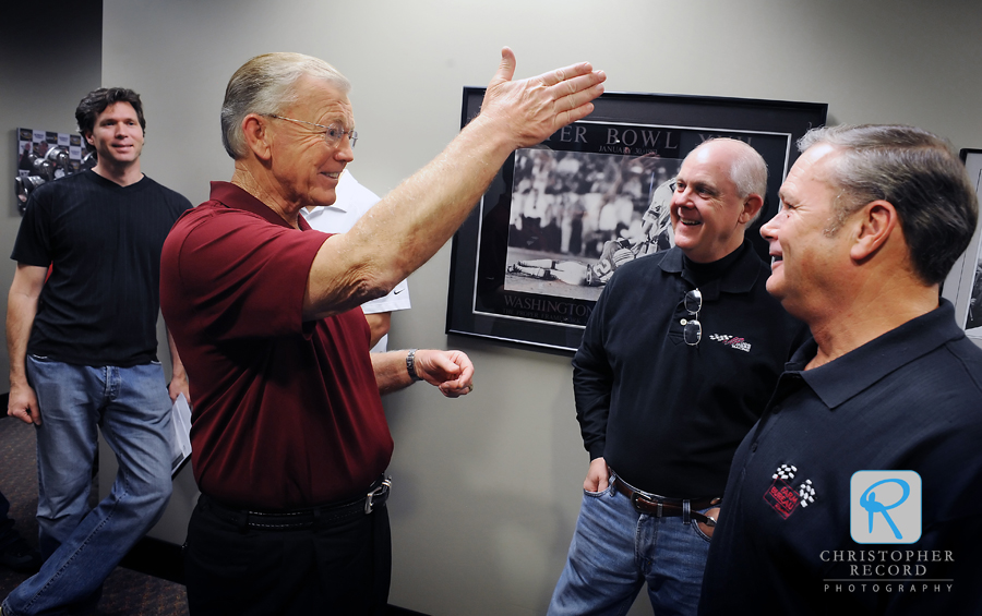 NASCAR race team owner and former NFL Coach Joe Gibbs, left, chats with Farm Bureau Insurance executives Tommy Doolittle, center, and Buddy Trosclair prior to filiming a commercial this week