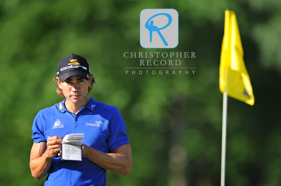 Camilo Villegas takes some notes during a practice session