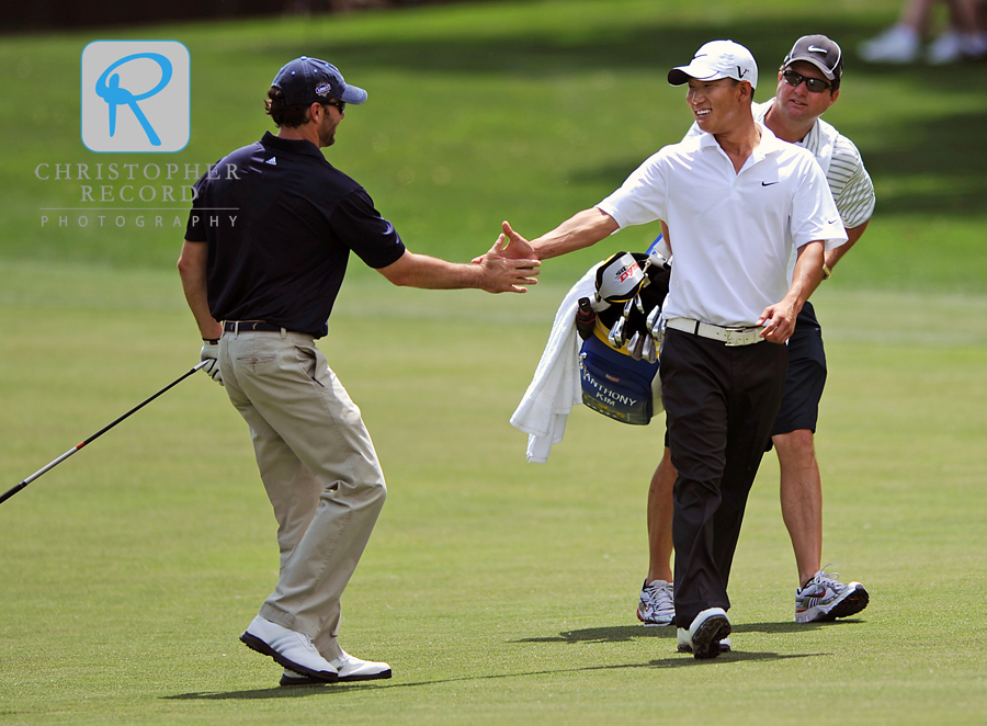 Anthony Kim congratulates playing partner and NASCAR racer Jimmie Johnson after Johnson hit a great shot in the Pro-Am