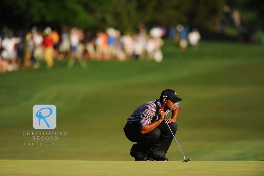 Tiger Woods lines up a putt in an early round