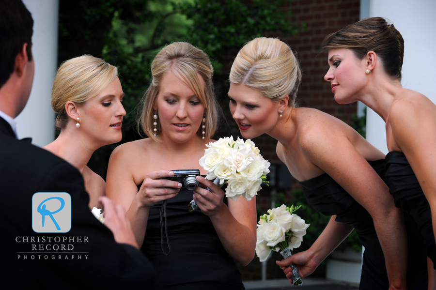 The bridesmaids check their photo skills