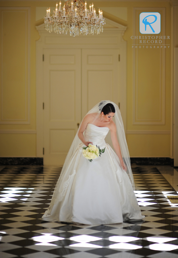 Bride fixes her dress during portrait sessin at Duke Mansion