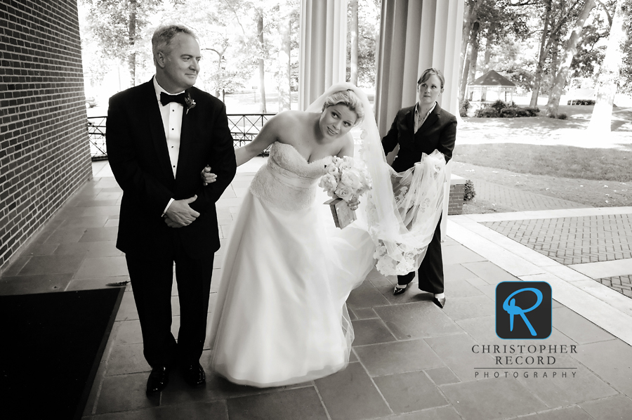 Elizabeth peaks back as Amy Horack of Dina Berg Blazek Events gives an assist with the veil
