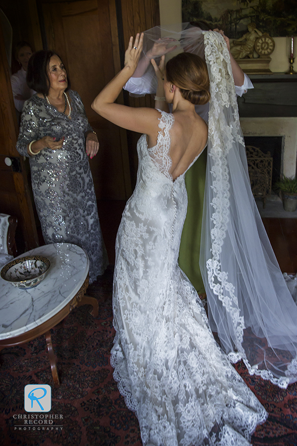 Camilla's mother helps line up the veil, the one she wore for her wedding